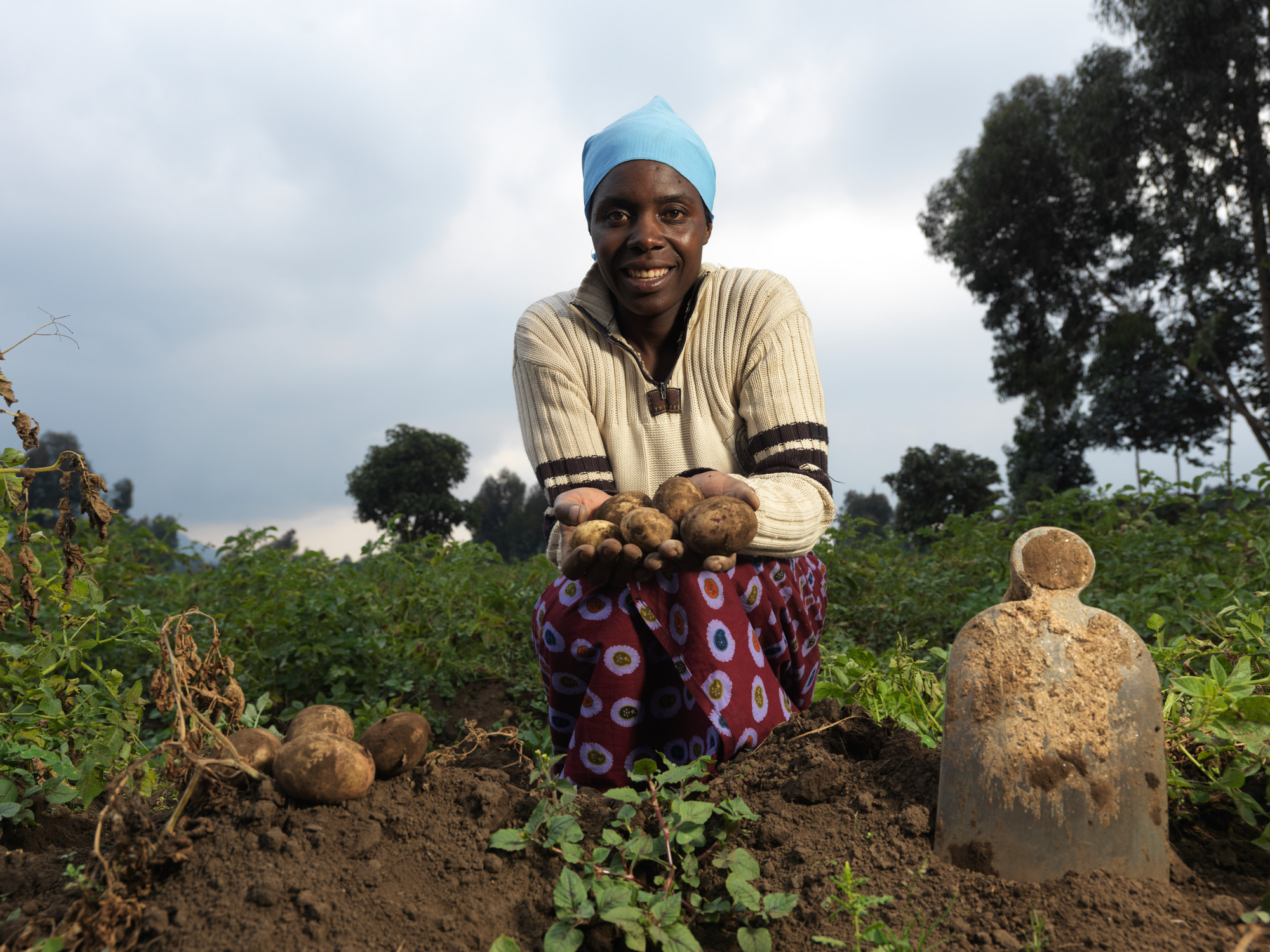 A woman kneels in a field and holds a handful of potatoes towards the camera.